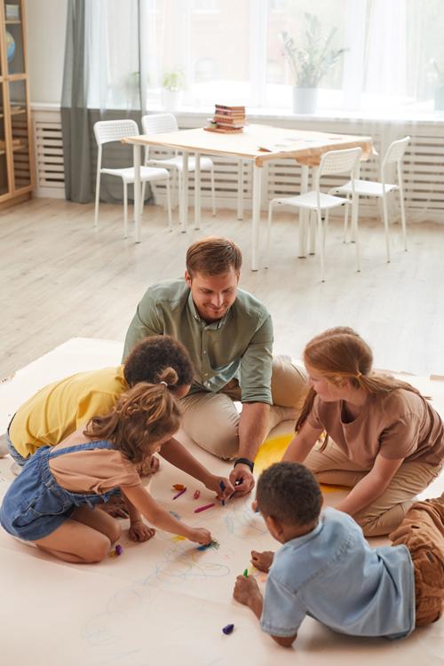 Erzieher malt mit Kindern